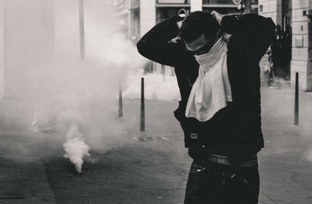 Man in protest wearing mask with tear gas lurking.
