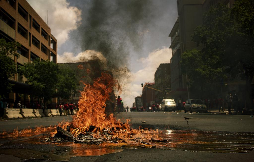 rubble on fire in the street as a result of rioters.