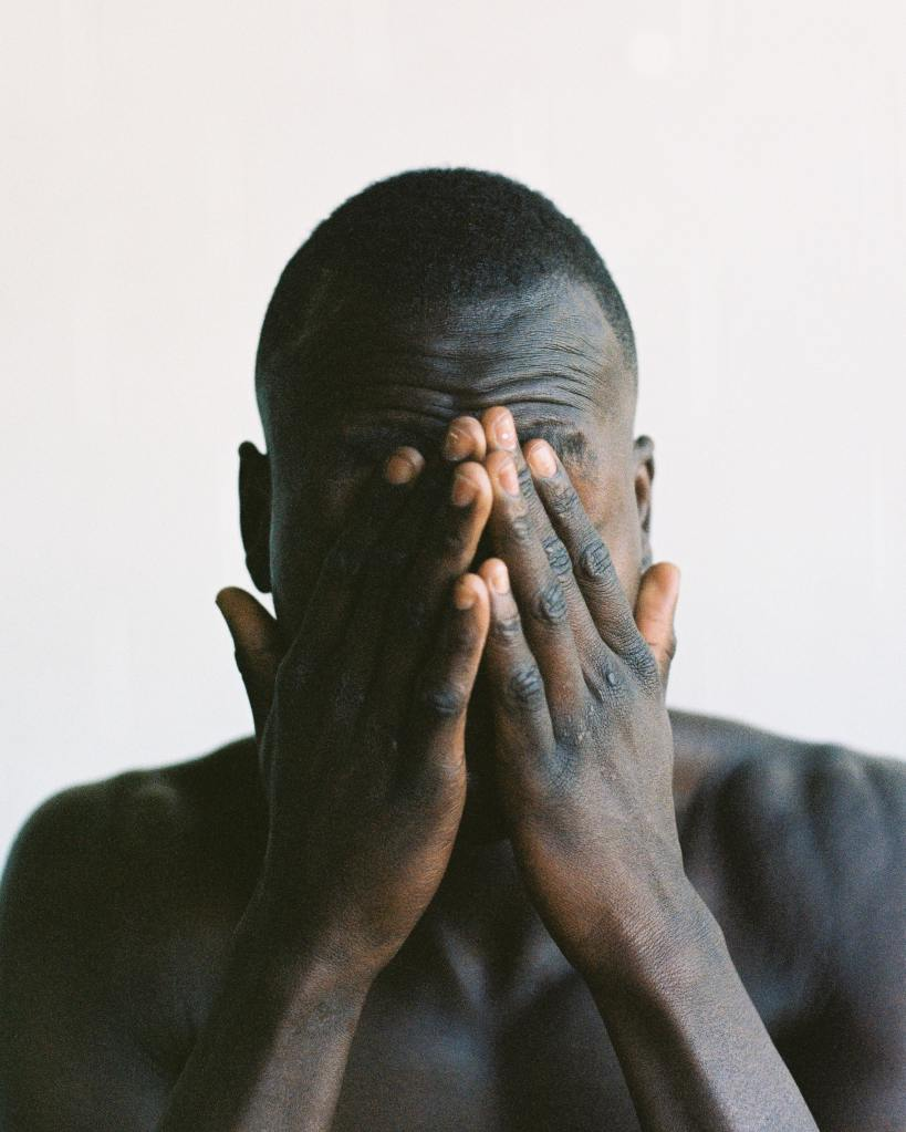 Black man covering his face with his hands.